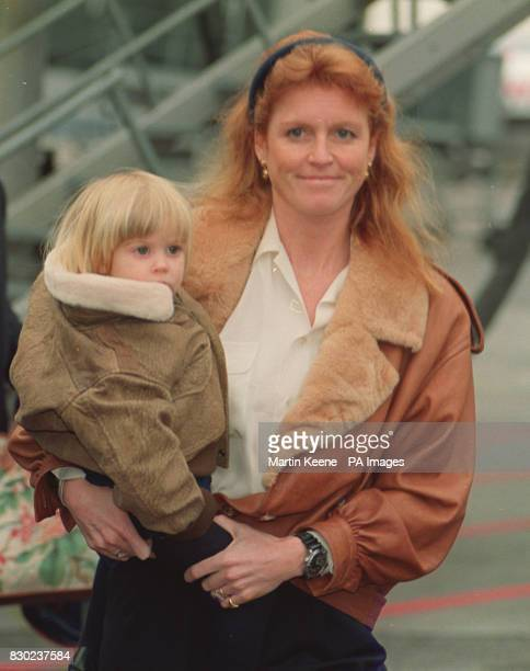 The Duchess of York carries her daughter Princess Beatrice to a waiting car at Zurich airport at the start of a private visit to Switzerland