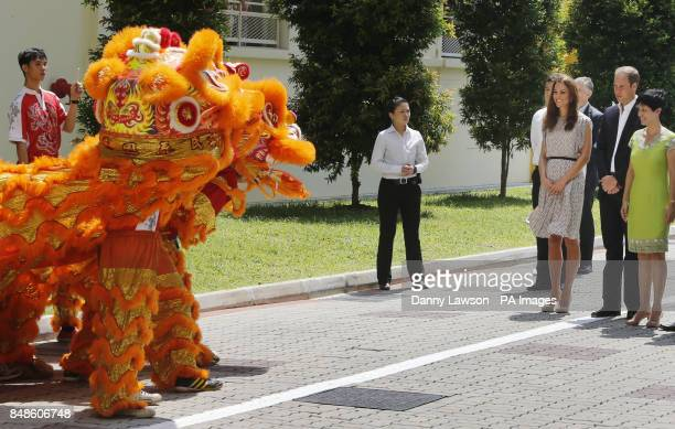 The Duke and Duchess of Cambridge look at a dancing dragon during a visit to Strathmore Green Queenstown Housing Estate in Singapore as part of a...