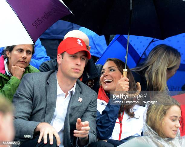 The Duke and Duchess of Cambridge use umbrellas as the rain falls during the Individual Eventing Jumping Final on day four of the London Olympic...