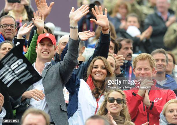 The Duke and Duchess of Cambridge with Prince Harry cheer and wave as Great Britain's Eventing team arrive to collect their medals during the...