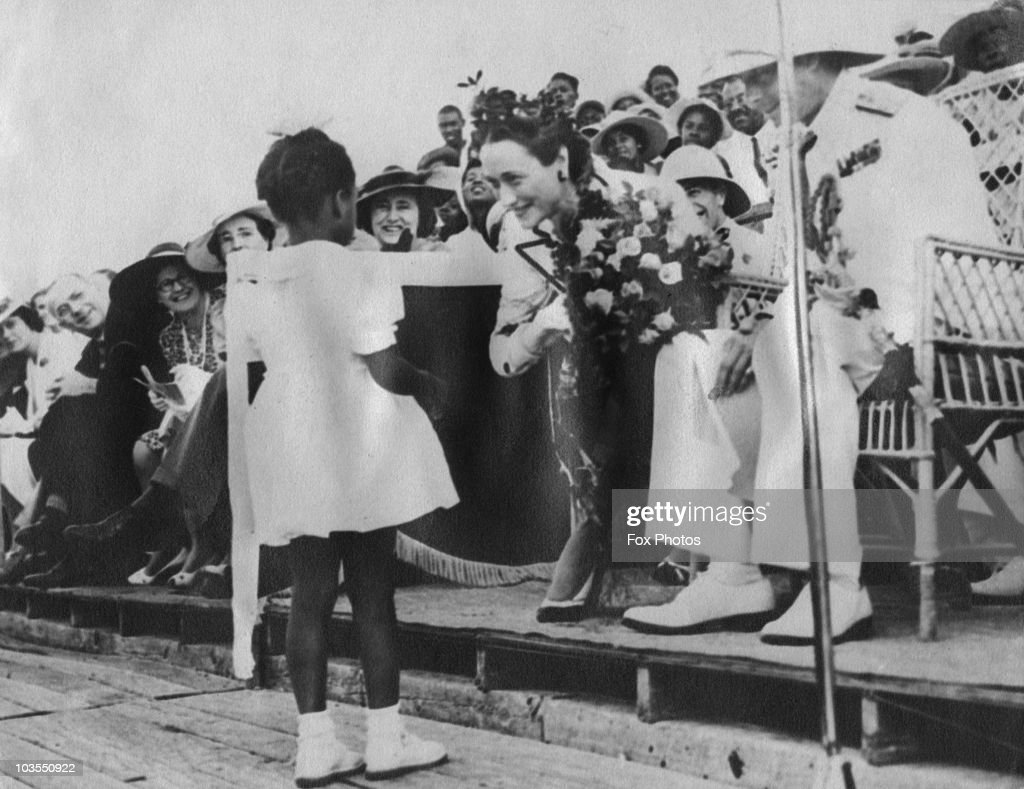 The Duke (1894 - 1972) and Duchess (1896 - 1986) of Windsor receive a bouquet of flowers from a little girl in Nassau, Bahamas, circa 1940.