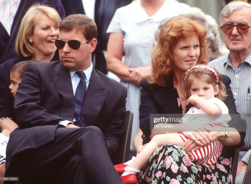 The Duke And Duchess Of York With Princess Eugenie At Upton House Sports Day. Eugenie Is Sitting On Her Mother's Lap. The Duke And Duchess Are Looking In Opposite Directions. Prince Andrew Is Wearing Sunglasses. Sarah Is Frowning.