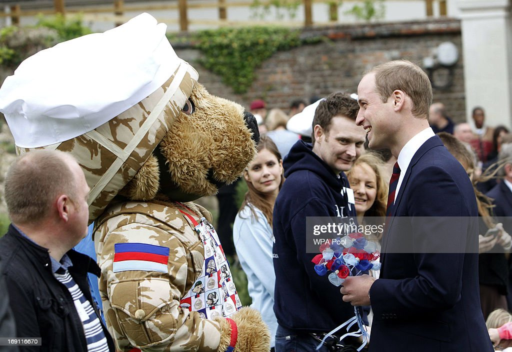 The Duke of Cambridge, Prince William (R) is presented with a posy as he speaks to a army bear during his visit to Tedworth House to officially open the charity's Tedworth House recovery centre on May 20, 2013 in Tidworth, England. During their visit the two Royal Princes met with wounded veterans, serving personnel, and their families. Tedworth House in Wiltshire is one of four new units in England which will offer respite care and rehabilitation to injured and sick service personnel, veterans and their families.