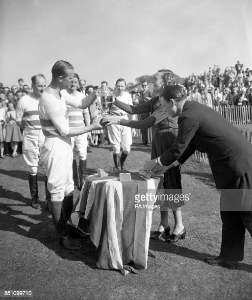The Duke of Edinburgh captain of the victorious Welsh Guards team receives the Combermere Cup from Countess Mountbatten after the final of the polo...