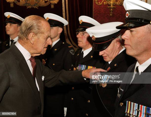 The Duke of Edinburgh examines a badge worn by Cecil McKee from Belfast during a reception for the Corps of Commissionaires in honour of their 150th...