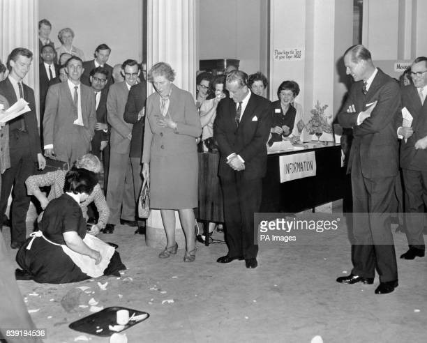 The Duke of Edinburgh folds his arms and joins in the general laughter as Joan Brackin kneels to clear up broken crockery at the Royal College of...