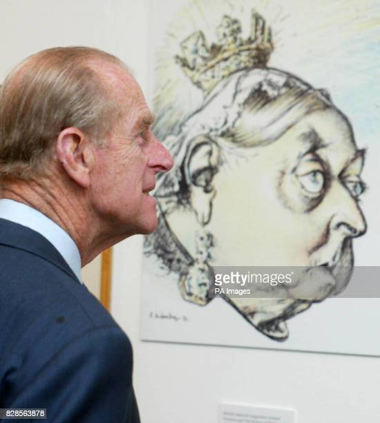 The Duke of Edinburgh looks at a cartoon of Queen Victoria by C Leandre from Le Rire magazine France 1897 during a visit to the Cartoon Art Trust's...