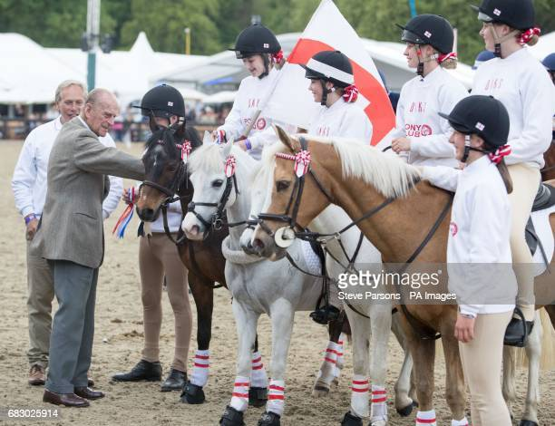 The Duke of Edinburgh presents the trophy and rosettes to team England who won the DAKS Pony Club Mounted Games at the Royal Windsor Horse Show which...