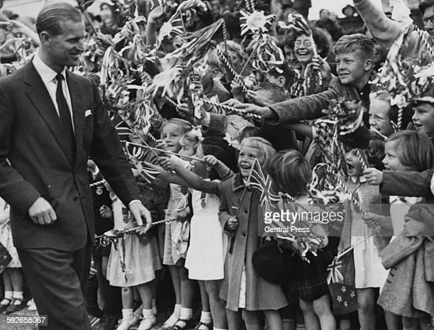 The Duke of Edinburgh walking past a crowd of cheering children waving Union Jack flags in Waipukurau circa 1954