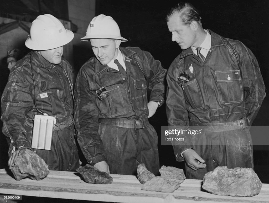 The Duke of Edinburgh wearing overalls as he inspects samples of pitchblende ore during a visit deep in to Port Radium uranium mine Canada August...
