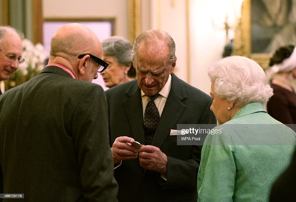 The Duke of of Edinburgh examines a commemorative Winston Churchill Medallion by designer Brian Clarke (left), as Queen Elizabeth II looks on, during the Winston Churchill Memorial Trust Reception at Buckingham Palace on March 18, 2015 in London, England.