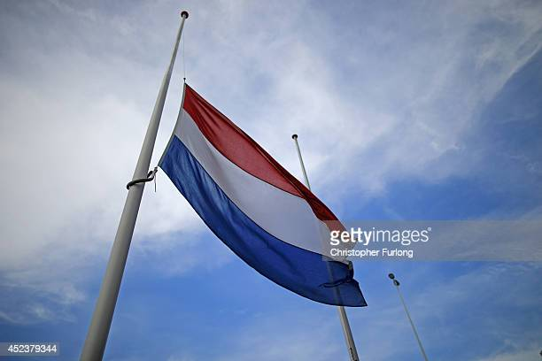 The Dutch flag flies at half mast at Schiphol Airport in memory of of Malaysia Airlines flight MH17 on July 19 2014 in Amsterdam Netherlands...