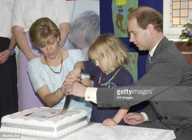 The Earl and Countess of Wessex cut the school birthday cake assisted by fouryearold Jesse Meyers at the Bagshot preschool centre at the Methodist...