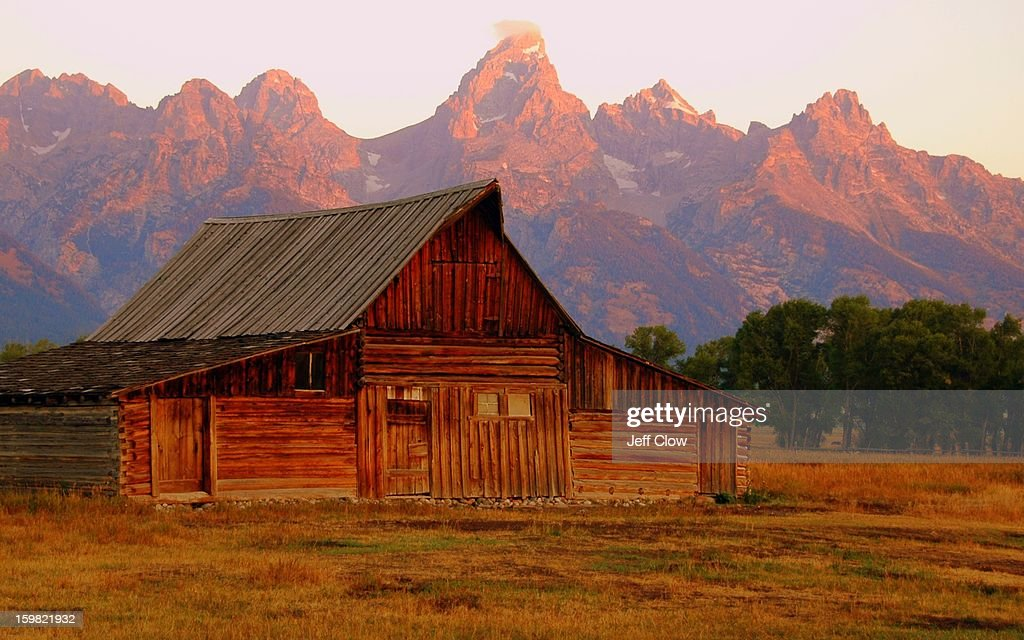 CONTENT] The early morning light - called alpenglow - turns the Grand Teton mountain range a particular shade of pink for a few brief seconds as the sun crests the horizon to the east. In the foreground is one of the barns built by early Mormon settler Thomas A. Moulton along Mormon Row in what is now Grand Teton National Park.