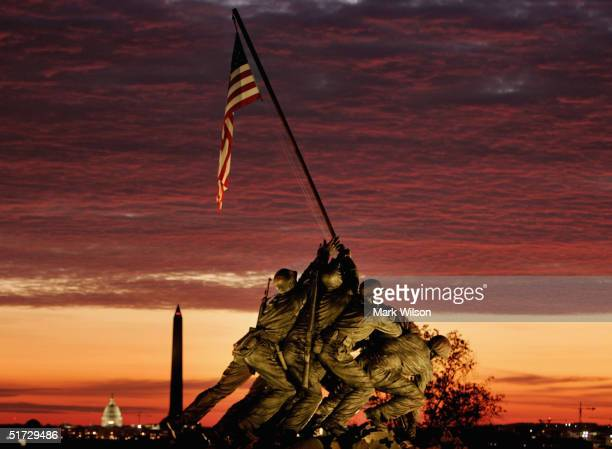 The early morning sun begins to rise behind the Iwo Jima Memorial on November 11 2004 in Arlington Virginia The 17th annual Veterans Day Parade along...
