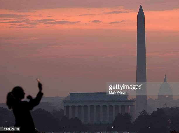 The early morning sun begins to rise behind the US Capitol Washington Monument and Lincoln Memorial on November 3 2016 in Arlington Virginia The...