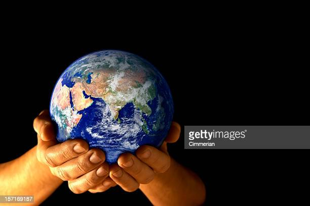The Earth held in cupped hands with a view of Asia