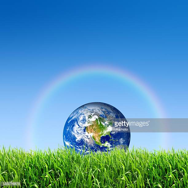 The earth on meadow with rainbow against a blue sky