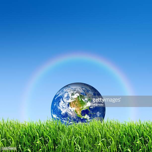 La Terre sur meadow avec arc-en-ciel dans le ciel bleu