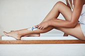 Cropped shot of a woman shaving her legs with a razor and shaving cream