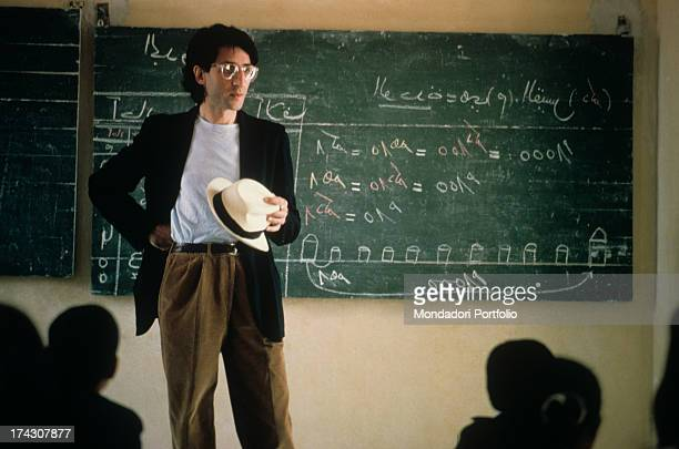 The eclectic Italian songwriter and singer from Sicily Francesco Battiato known as Franco Battiato is standing in silence behind him a blackboard and...