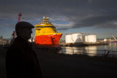The Edda Ferd platform supply shipping vessel operated by Ostensjo Rederi AS sits docked as oil storage silos operated by Caledonian Oil Ltd stand on...