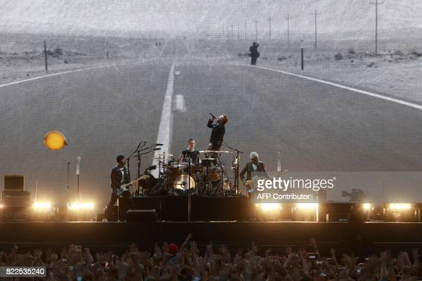 TOPSHOT The Edge Larry Mullen Jr Bono and Adam Clayton of Irish rock band U2 perform on stage at the Stade de France in SaintDenis outside Paris on...
