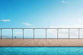The edge swimming pool on the building balcony with blue sky background