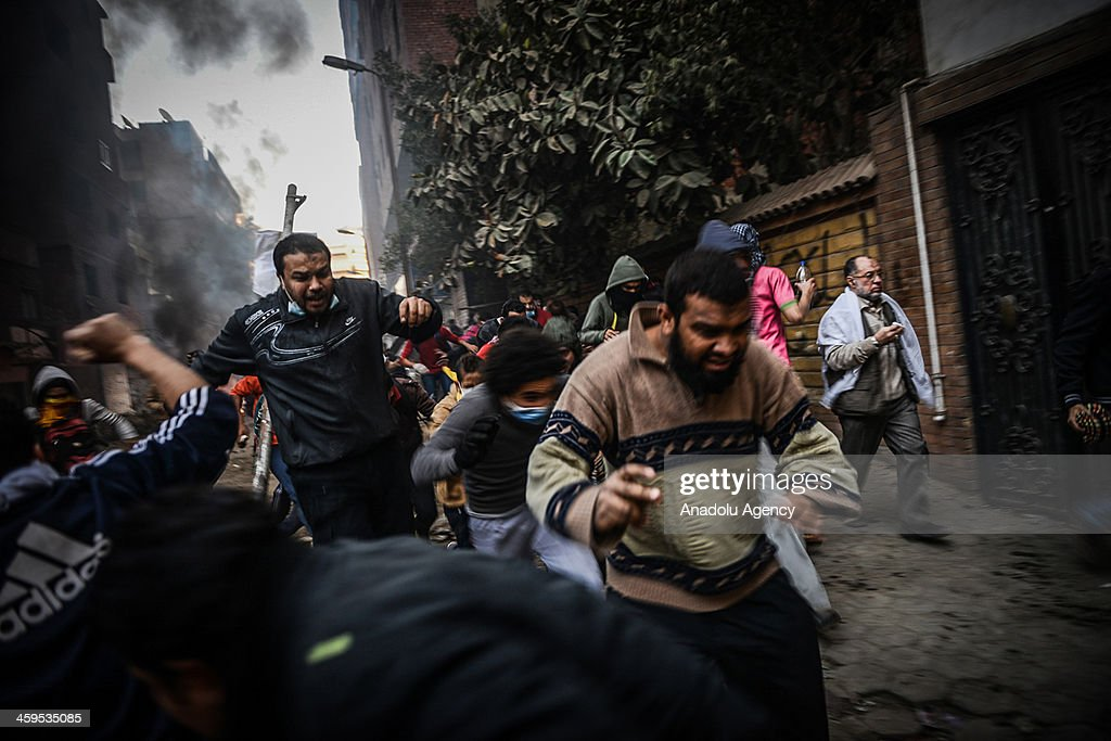 The Egyptian demonstrators escape from tear gas during the clashes between Egyptian police and pro-democracy protesters after declaring the Muslim Brotherhood as a terrorist group in Alf Maskan district of Cairo, Egypt, December 27, 2013.