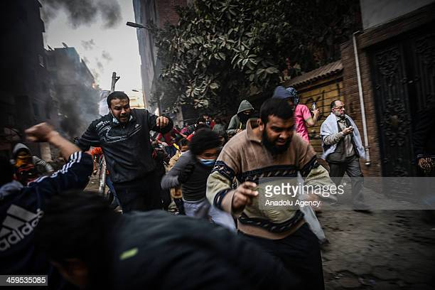 The Egyptian demonstrators escape from tear gas during the clashes between Egyptian police and prodemocracy protesters after declaring the Muslim...