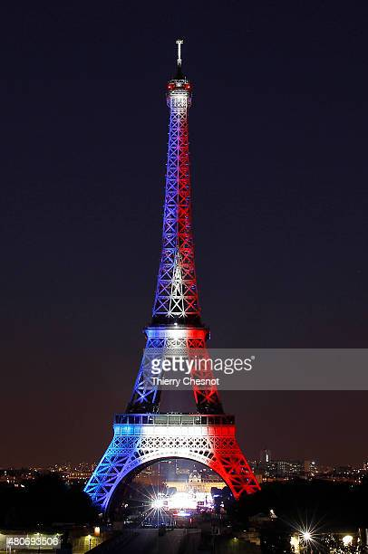 The Eiffel Tower is enlighted with colors of the French national flag prior to the beginning of the fireworks on July 14 2015 in Paris France...