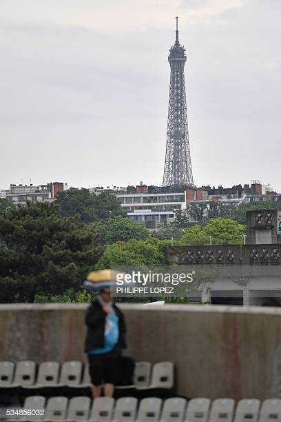 The Eiffel Tower is seen in the background as a woman holding an umbrella leaves the stands after rain interrupted play during the women's third...
