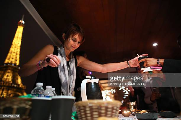 The Eiffel Tower is seen in the background as a woman serves drinks at a Christmas Eve dinner organized by French charitable organization 'Secours...