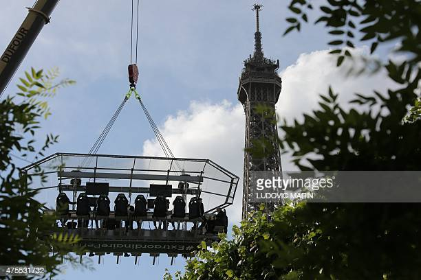 The Eiffel Tower is seen in the background as people sit around a table suspended 30 meters above the ground and watch Roland Garros 2015 French...
