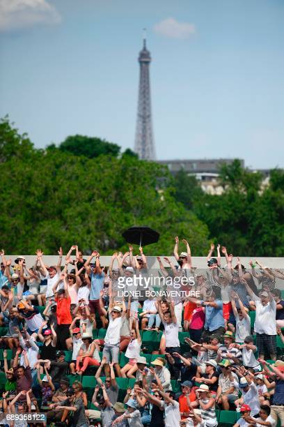 The Eiffel Tower is seen in the background as the crowd cheers during a tennis match on the Philippe Chatrier court at the Roland Garros 2017 French...