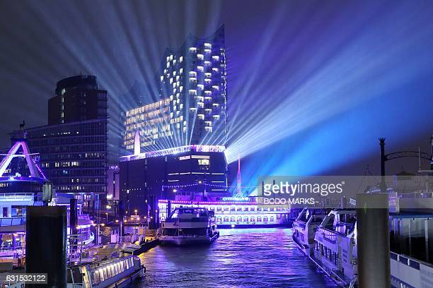 The Elbphilharmonie concert hall is surrounded by light rays next to the harbour during its opening light show on January 11 2017 in Hamburg northern...