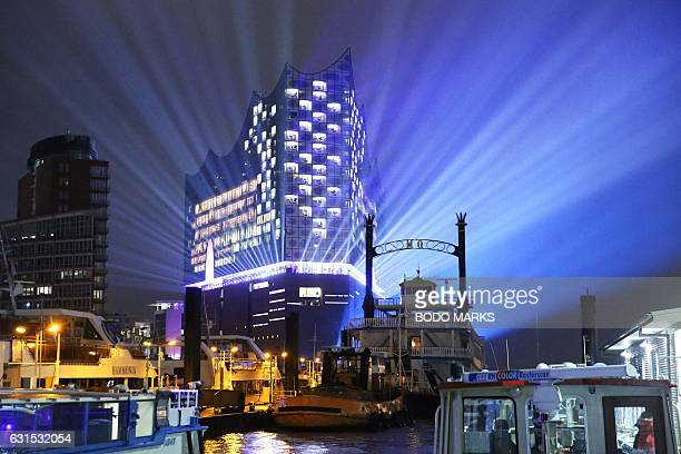 The Elbphilharmonie concert hall is surrounded by sends light rays next to the harbour during its opening light show on January 11 2017 in Hamburg...