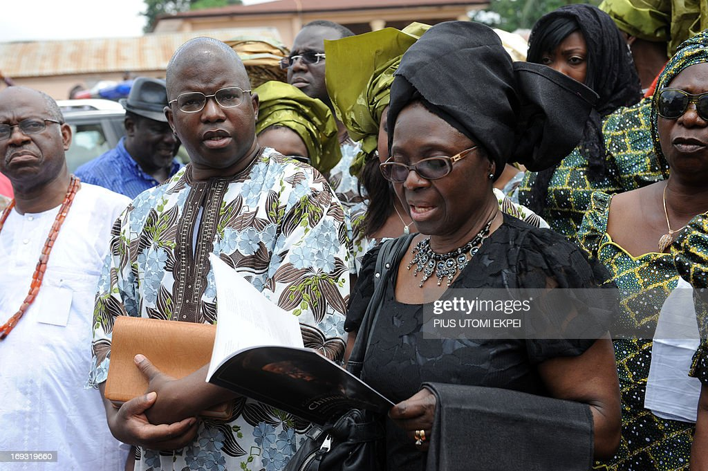 The elderly son Dr. Ikechukwu Achebe (C) and the widow Professor Christie Achebe sing hymns to accompany the body of late literary icon Professor Chinua Achebe to St. Phillips Anglican Church for the funeral at Ogidi in southeast Nigeria on May 23, 2013. Renowned author Professor Chinua Achebe was buried at his Ogidi country home. Hundreds of mourners gathered on Thursday in the hometown of Nigerian novelist Chinua Achebe for the funeral of the man regarded as the father of modern African literature and the author of the widely praised 'Things Fall Apart.'