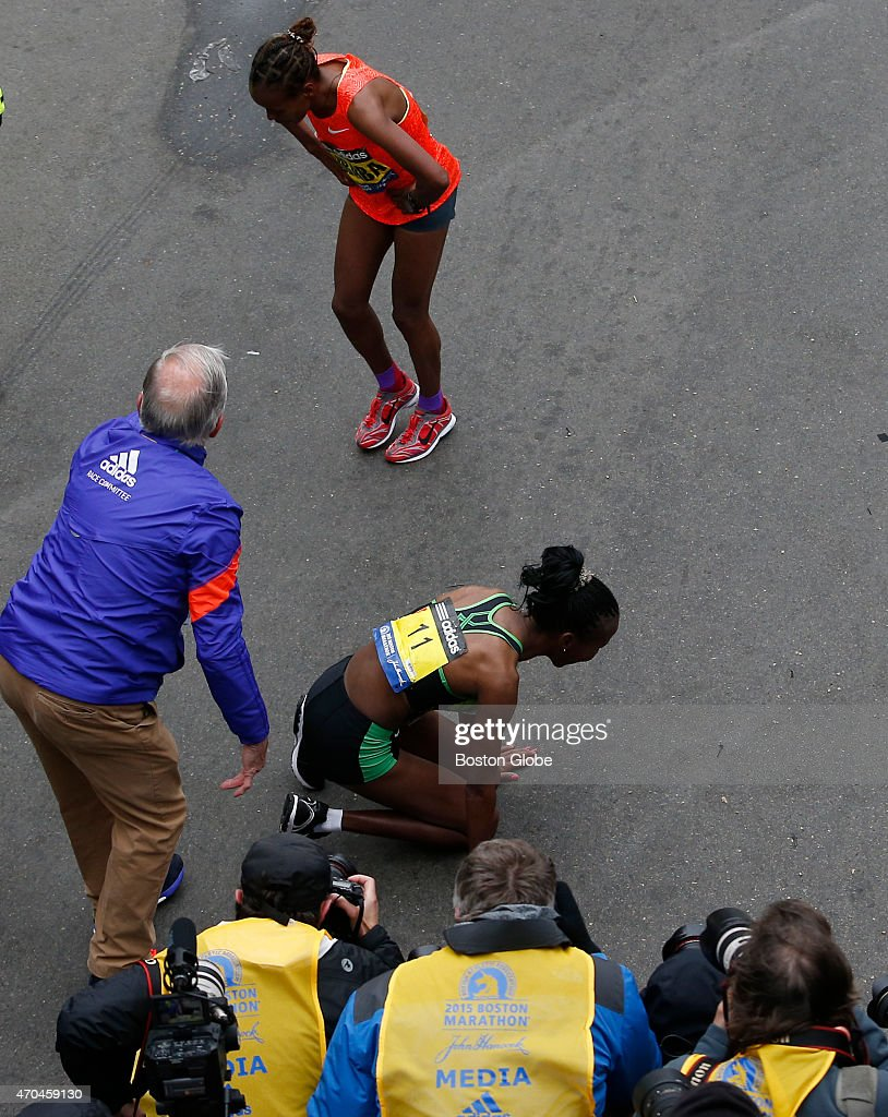 The Elite Womens division winner <a gi-track='captionPersonalityLinkClicked' href=/galleries/search?phrase=Caroline+Rotich&family=editorial&specificpeople=14407354 ng-click='$event.stopPropagation()'>Caroline Rotich</a>, center, falls to her knees after crossing the Boston Marathon finish line. Second place finisher Mare Dibaba crosses behind her.