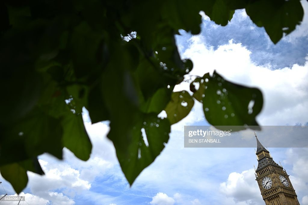 The Elizabeth Tower (R) which houses the 'Big Ben' bell in the Palace of Westminster is viewed through the leaves of a tree in central London on June 28, 2016. EU leaders attempted to rescue the European project and Prime Minister David Cameron sought to calm fears over Britain's vote to leave the bloc as ratings agencies downgraded the country. Britain has been pitched into uncertainty by the June 23 referendum result, with Cameron announcing his resignation, the economy facing a string of shocks and Scotland making a fresh threat to break away. / AFP / BEN