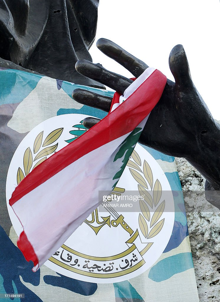The emblem of the Lebanese Army that reads in Arabic, 'Honor, Sacrifice and Loyalty' and the national flag hang from the plinth and hand of the statue in Martyr's Square, in downtown Beirut, on June 25, 2013, during a rally in support of the army a day after 17 soldiers died in clashes against fighter loyal to radical Sunni Muslim cleric Ahmad al-Assir, in the southern port city of Sidon.