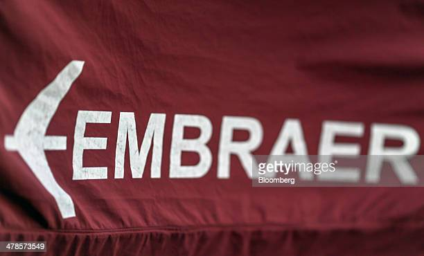 The Embraer SA logo is displayed on a banner at the India Aviation 2014 air show held at the Begumpet Airport in Hyderabad India on Thursday March 13...