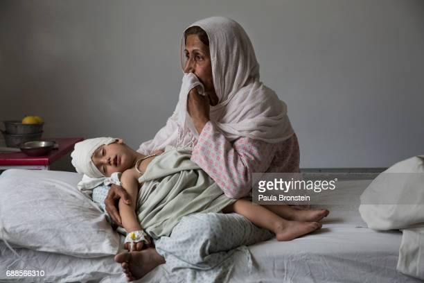 A the Emergency hospital Najiba holds her nephew Shabir age 2 who was injured from a bomb blast which killed his sister in Kabul on March 29 2016...