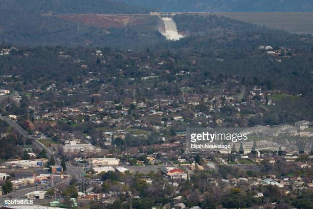 The emergency spillway and the damaged main spillway are seen behind the town of Oroville from the air on February 13 2017 in Oroville California...
