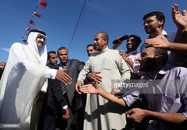 The Emir of Qatar Sheikh Hamad bin Khalifa alThani greets locals as he arrives for a cornerstonelaying ceremony of a Qatarifunded rehabilitation...