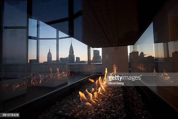 The Empire State and Chrysler buildings are seen through a fireplace in the penthouse apartment at the 50 United Nations Plaza building in New York...