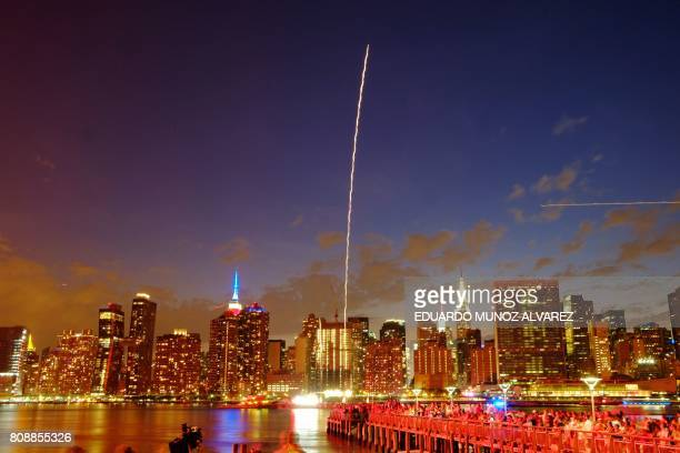 TOPSHOT The Empire State Building and the Christal Building are seen during the Macy's 4th of July fireworks show from Queens New York on July 4 2017...