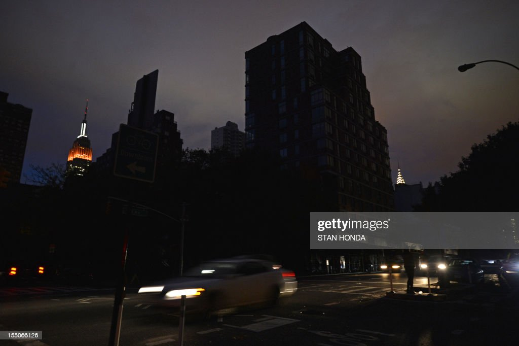 The Empire State Building (L) and the Chrysler Building (R) are seen behind darkend buildings on Second Avenue October 31, 2012 in New York as power is still out south of 34th Street due to Hurricane Sandy. AFP PHOTO/Stan HONDA