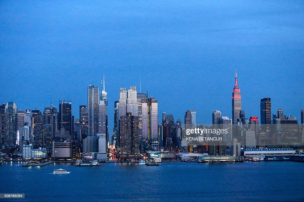 The Empire State Building in New York City is lit in red and gold in honor of the Chinese Lunar New Year, as seen from Weehawken, New Jersey, February 6, 2016. BETANCUR