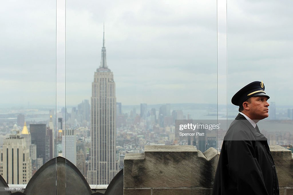 The Empire State Building is viewed as a guard walks along the observation deck at Rockefeller Center on August 24, 2010 in New York City. A proposed tower on 34th Street would stand only 900 feet away from the iconic Empire State Building if it were to be completed. The new tower, which would be built at 15 Penn Plaza, has drawn criticism from the owners of the 102-storey Empire State Building, who say that at its current proposed height it would be just 34 feet shorter than the Empire State building and would severely alter the view of the Manhattan skyline. Standing at 1,250 feet at the 102nd floor, the Empire State building is currently the tallest building in New York.